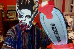 Thomas Outt in paper mask made from Midnites For Maniacs Poster designed by Jesse Hawthorne Ficks, brandishing a fake chainsaw, all forlorn about not being cast in the remake of THE TEXAS CHAINSAW MASSACRE!