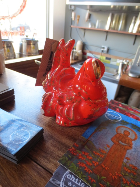 This sweet ceramic chicken greets you, but quietly.  She has a reddish-orange charm. Now, what might that be?  Drop by & find out!