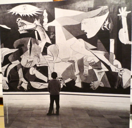 Photograph showing the size of the original Guernica with a boy as a viewer.
